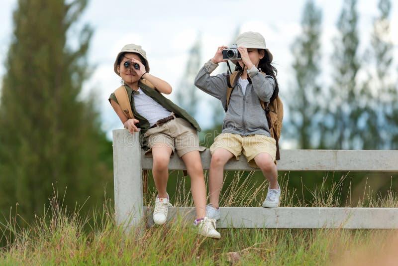 Crianças asiáticas e amigas tiram uma foto e veem binóculos para aventura e turismo para viagens de destino e lazer para educaà imagem de stock