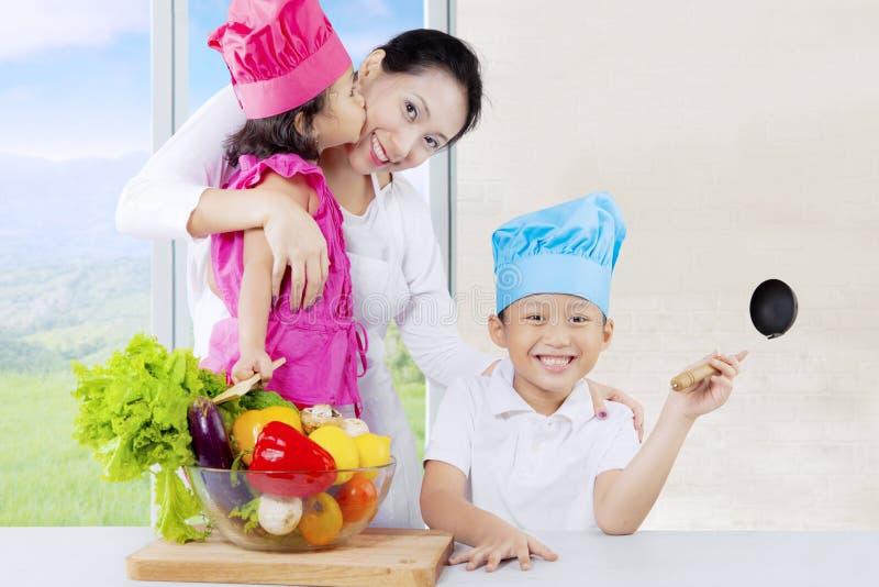Crianças asiáticas e mamã prontas para cozinhar imagem de stock royalty free