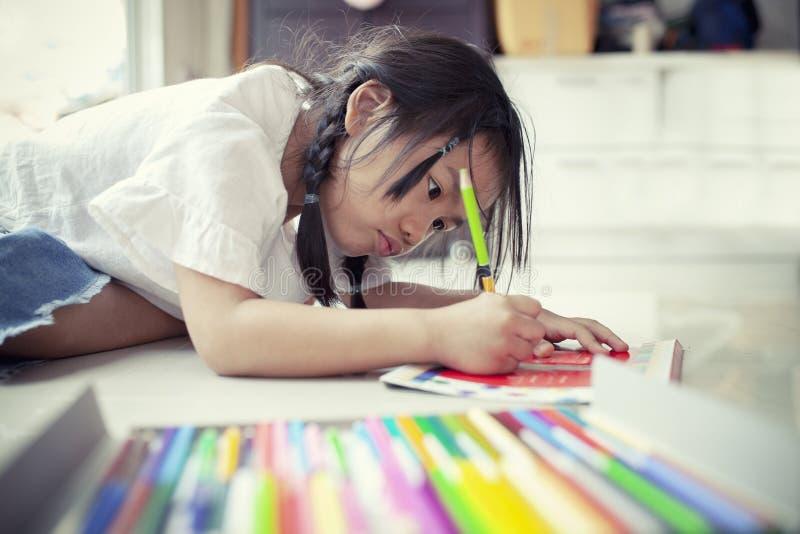 Crianças asiáticas que jogam e que pintam o lápis da cor no livro de papel mim fotografia de stock