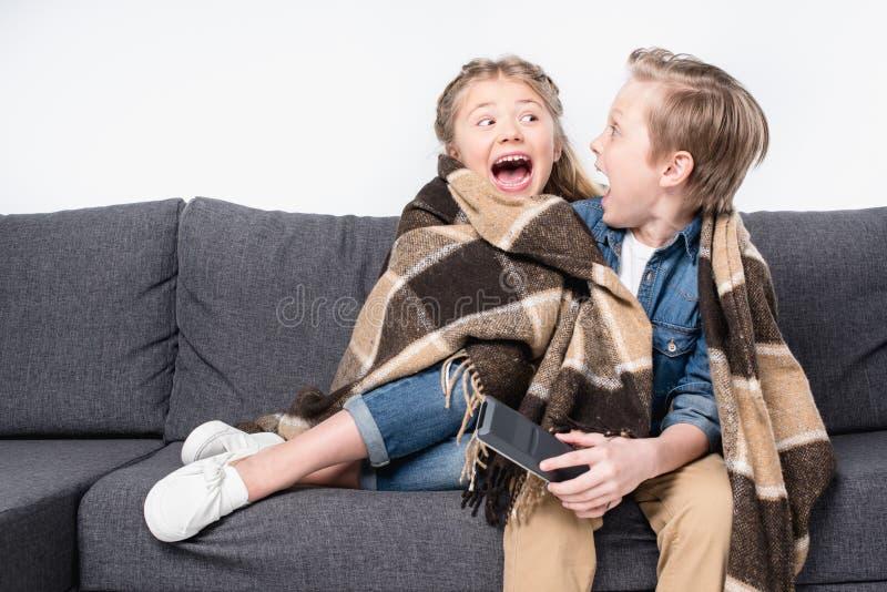 Crianças assustado na cobertura que senta-se no sofá e que olha se imagem de stock