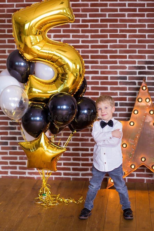 Crianças bonitas, rapazes pequenos que comemoram o aniversário e que fundem velas no bolo cozido caseiro, interno Festa de anos p fotos de stock