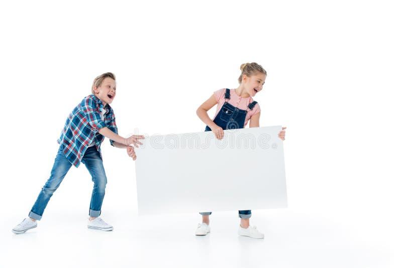 Crianças bonitos alegres que têm o divertimento com cartaz vazio foto de stock