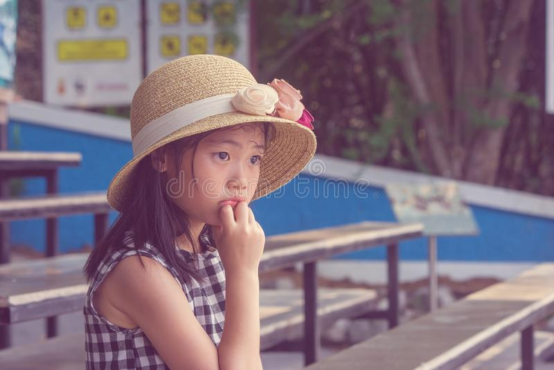 Crianças bonitos asiáticas sós que vestem o chapéu do weave e que sentam-se na cadeira longa de madeira, ela que olha para a fren fotos de stock