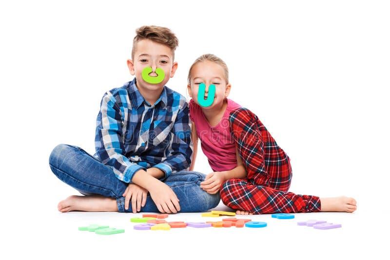 Crianças bonitos com grandes letras coloridas do alfabeto no fundo branco Conceito da terapia da fala das crianças Fundo do imped imagem de stock
