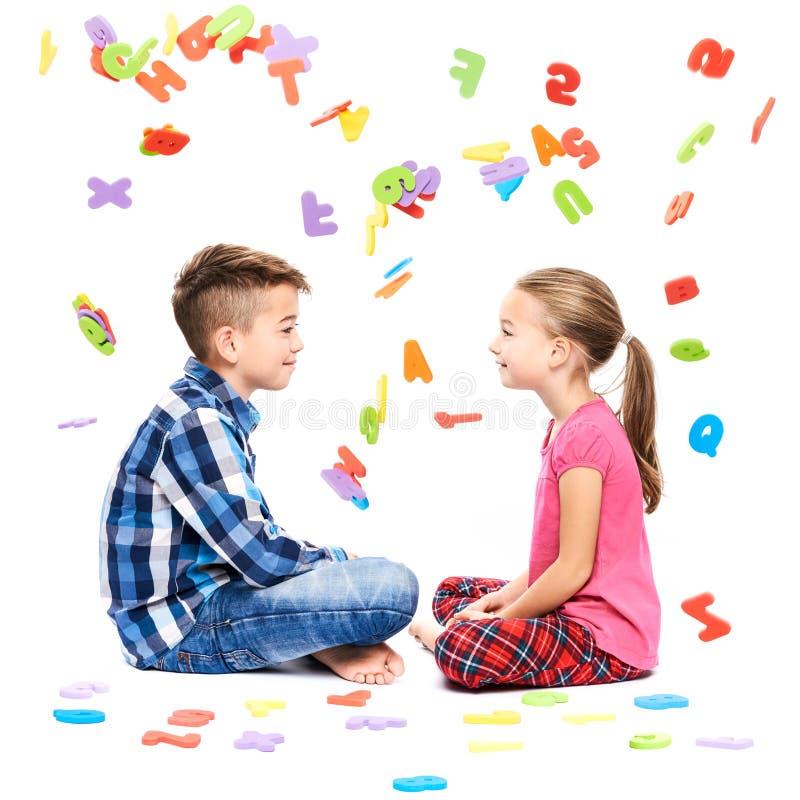 Crianças bonitos com grandes letras coloridas do alfabeto no fundo branco Conceito da terapia da fala das crianças Fundo do imped imagens de stock