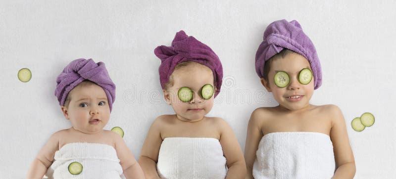Crianças bonitos com turbantes e pepinos do banho imagem de stock