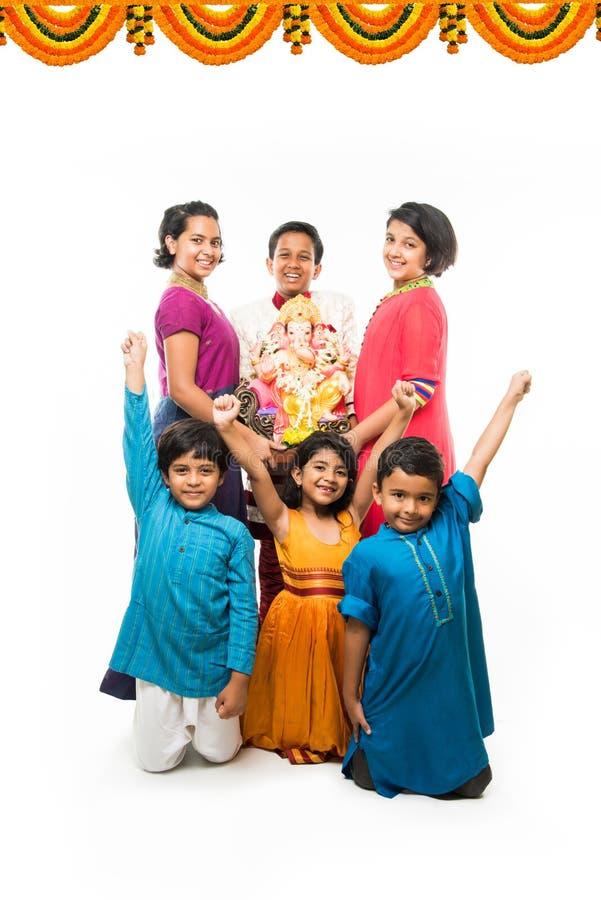 Crianças bonitos indianas que guardam a estátua de Lord Ganesha ou de Ganapati no festival ou no chaturthi de Ganesh, dando boas- imagens de stock royalty free