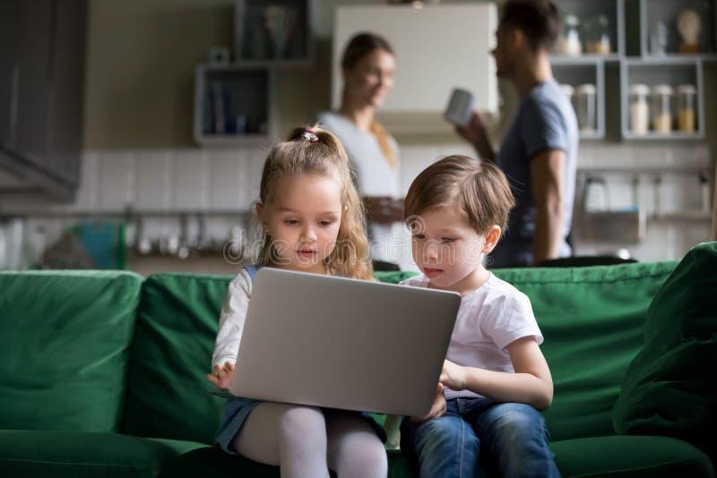 Crianças bonitos irmã e irmão que guardam o portátil que olha em linha imagem de stock