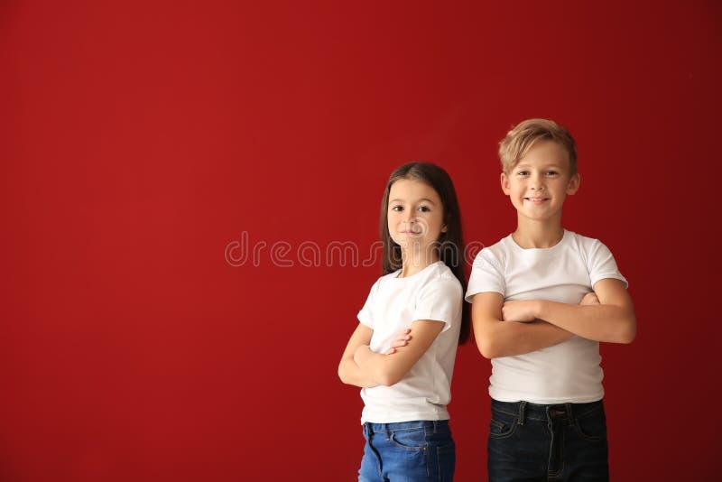 Crianças bonitos nos t-shirt no fundo da cor fotos de stock