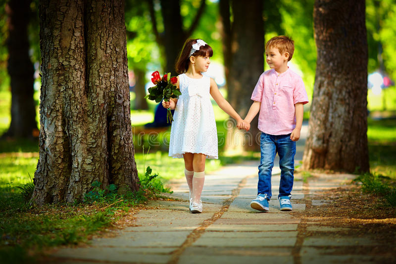 Crianças bonitos que andam junto no parque do verão fotografia de stock royalty free