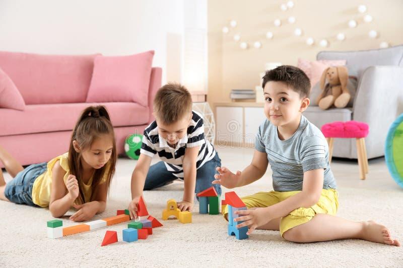 Crianças bonitos que jogam com blocos de apartamentos no assoalho, dentro fotos de stock royalty free