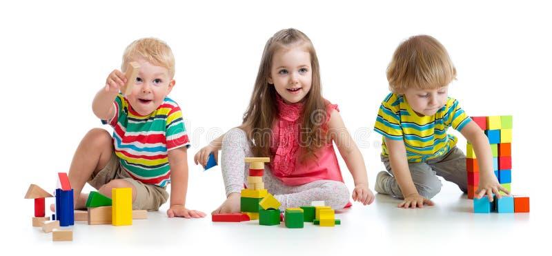 Crianças bonitos que jogam com brinquedos ou blocos e que têm o divertimento ao sentar-se no assoalho isolado sobre o fundo branc imagem de stock