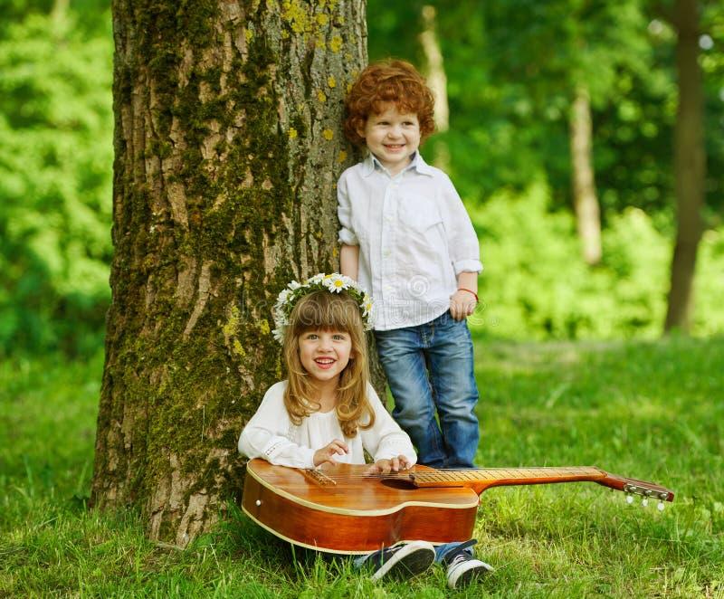 Crianças bonitos que jogam a guitarra fotografia de stock royalty free