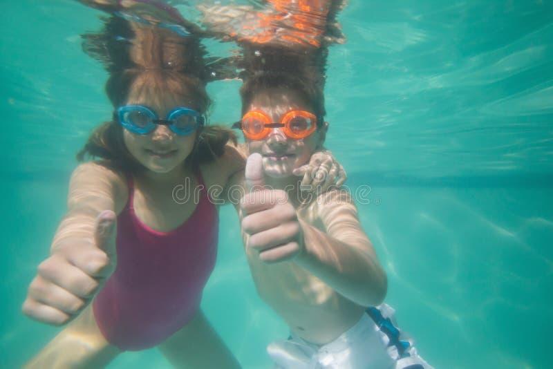 Crianças bonitos que levantam debaixo d'água na associação fotografia de stock