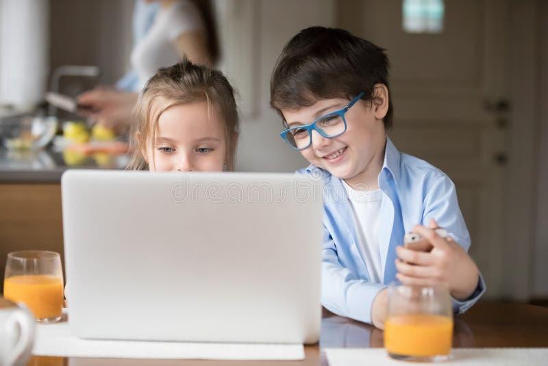 Crianças bonitos que olham desenhos animados em linha no portátil imagens de stock