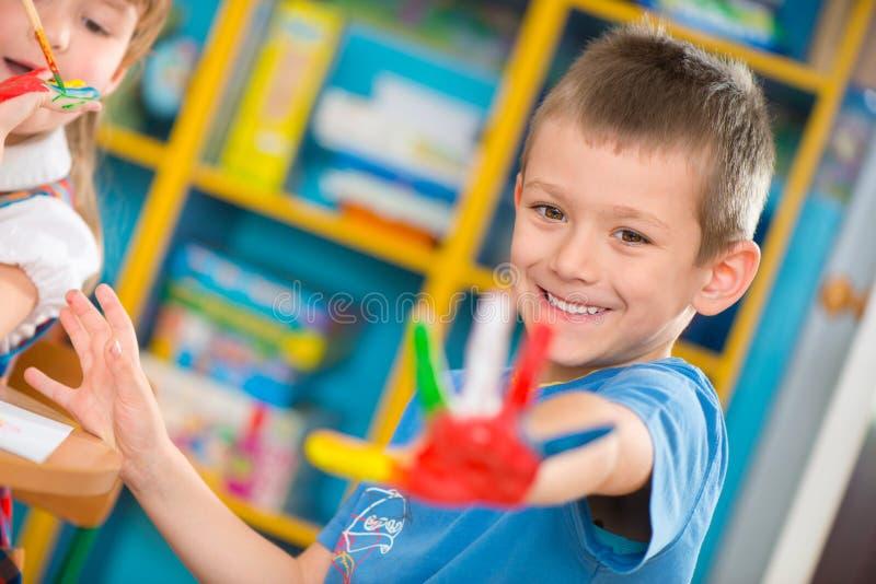 Crianças bonitos que pintam no jardim de infância fotografia de stock royalty free