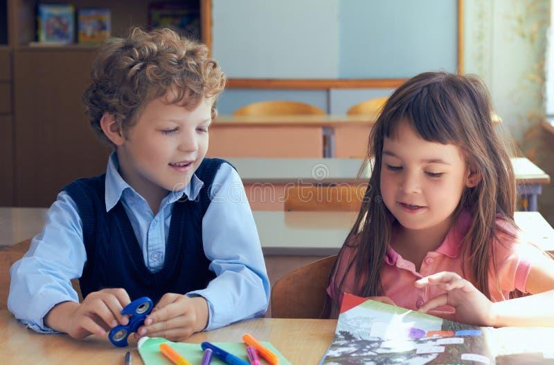 Crianças bonitos que sentam-se na mesa na sala de aula Conceito da primeira lição na escola primária fotos de stock