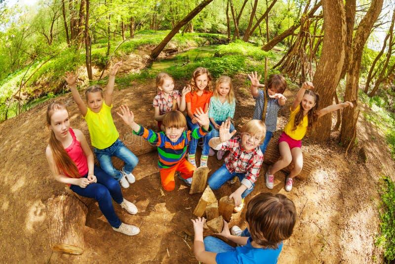 Crianças bonitos que têm o divertimento com suas mãos acima na floresta imagem de stock royalty free