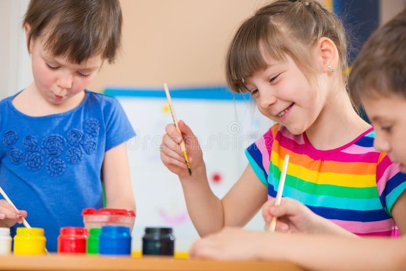 Crianças bonitos que tiram com pinturas coloridas no jardim de infância imagem de stock royalty free