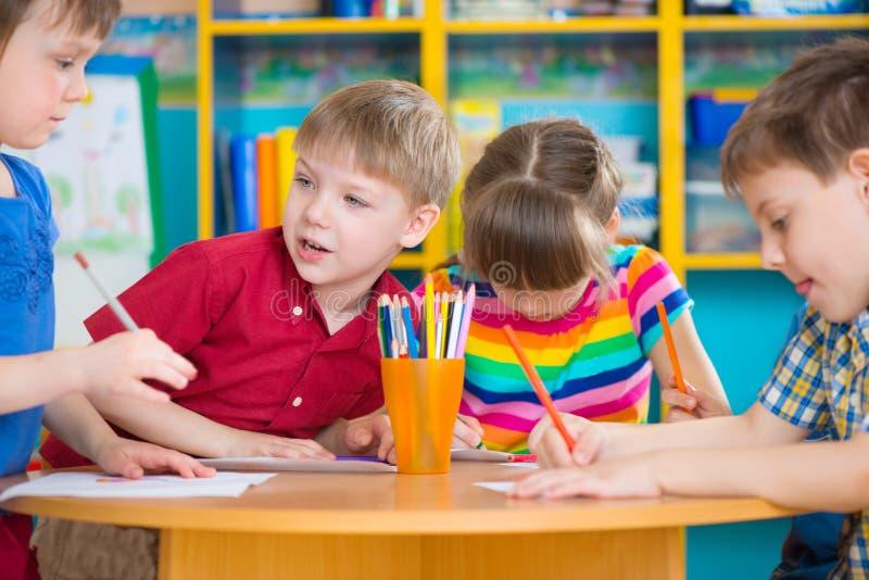 Crianças bonitos que tiram com pinturas coloridas no jardim de infância fotos de stock royalty free