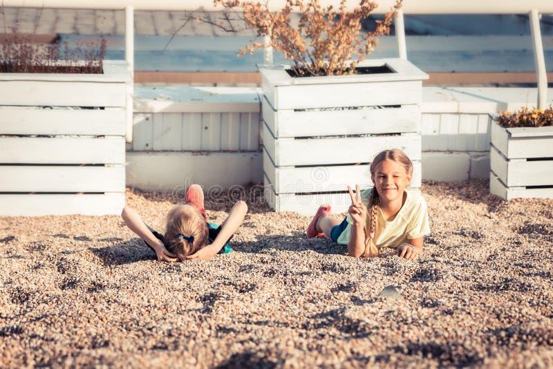 Crianças brincalhão felizes que têm o divertimento junto no estilo de vida despreocupado da infância da praia do verão fotografia de stock royalty free