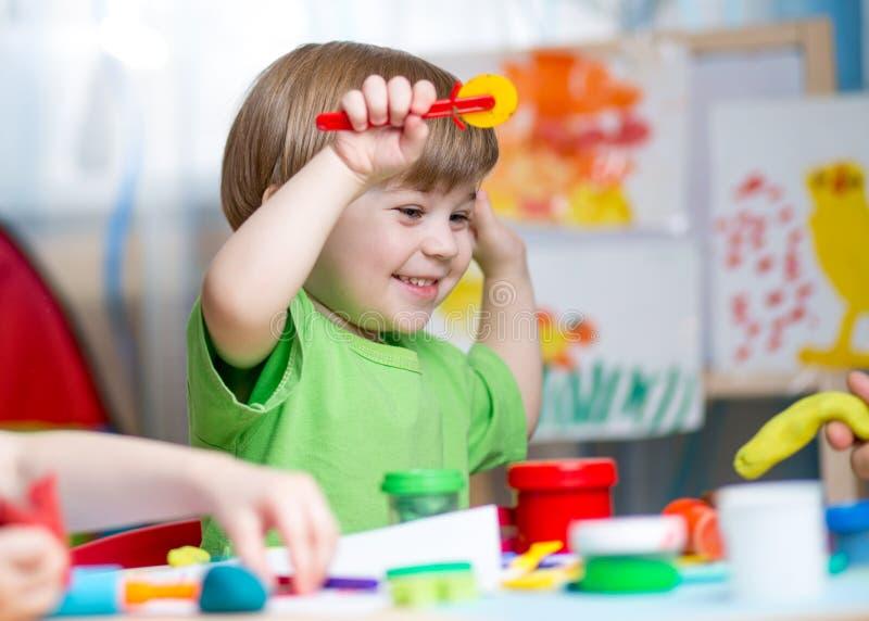 Crianças com argila do jogo em casa fotografia de stock