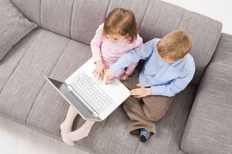 Crianças com computador portátil fotografia de stock royalty free