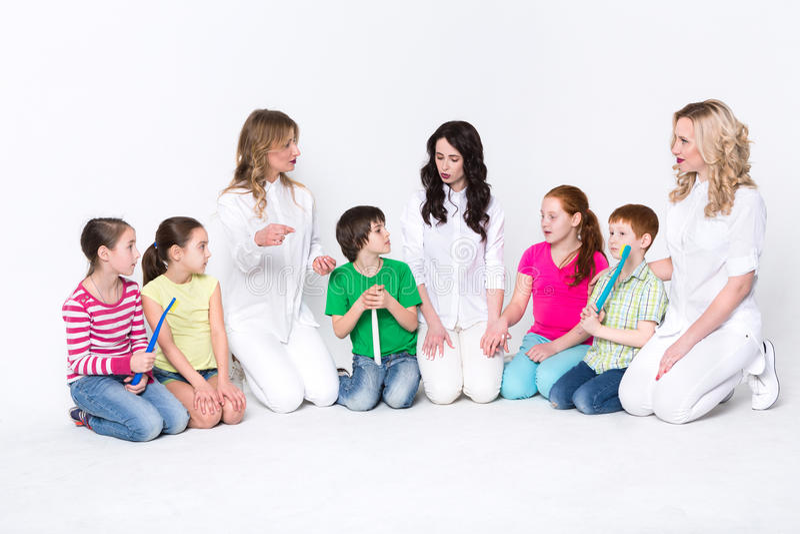 Crianças com escovas de dentes e doutores no branco imagem de stock royalty free