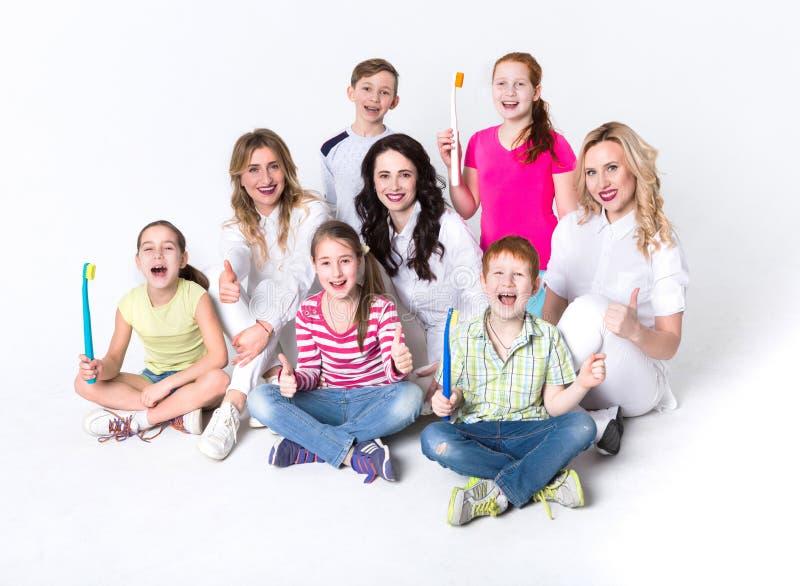 Crianças com escovas de dentes e doutores no branco imagens de stock
