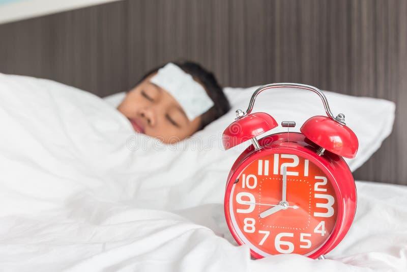Crianças com febre fresca na testa e sono na cama imagens de stock