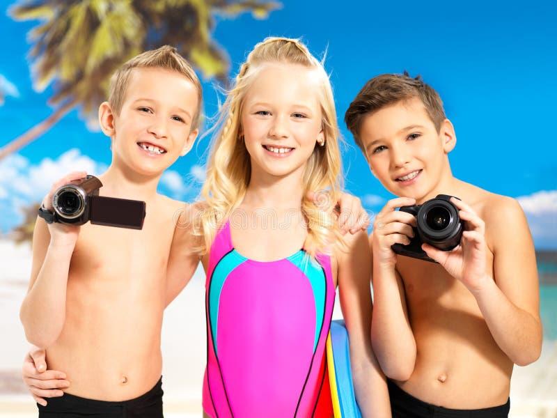 Crianças com foto e câmara de vídeo na praia. foto de stock royalty free