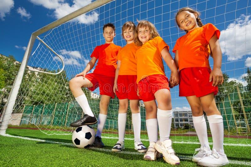Crianças com futebol em seguido perto da carpintaria foto de stock