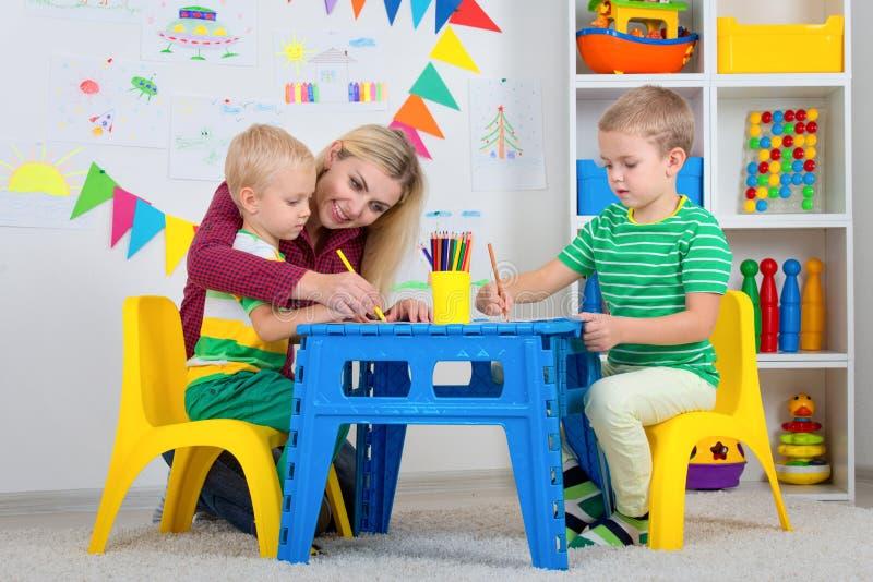 Crianças com imagens da mamã e da tração na sala das crianças fotos de stock