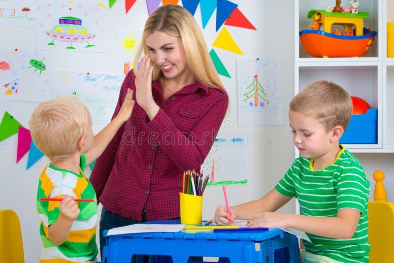 Crianças com imagens da mamã e da tração na sala das crianças fotografia de stock