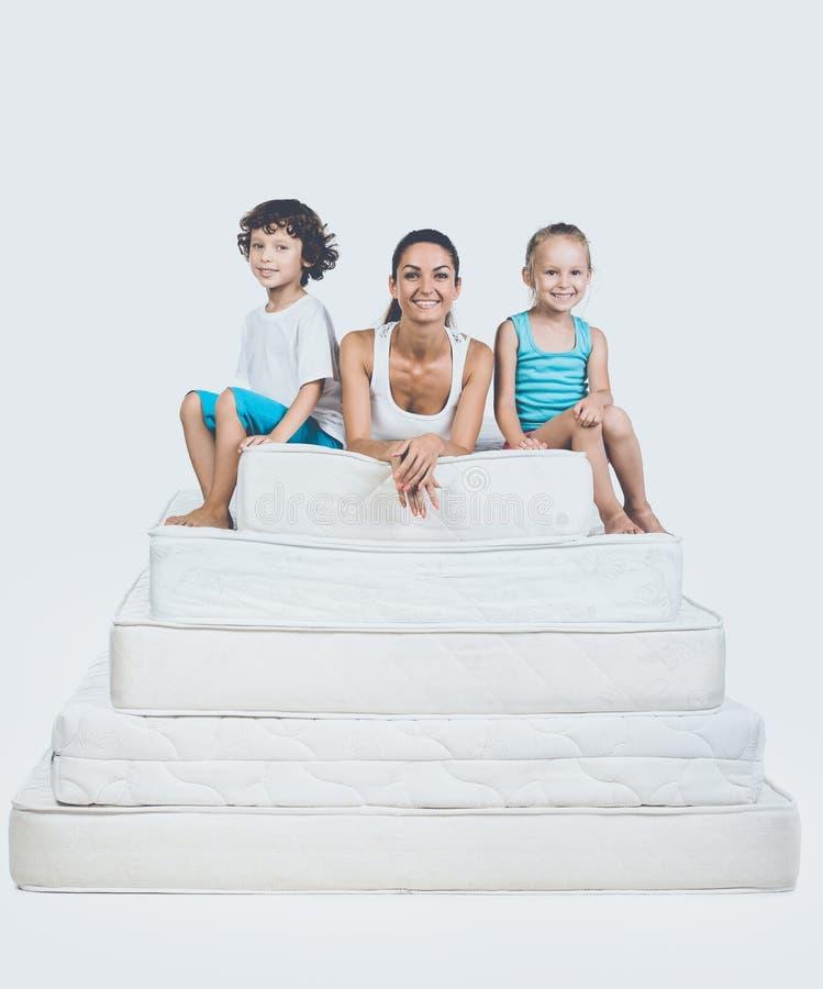 Crianças com a mãe que senta-se na pirâmide do colchão foto de stock