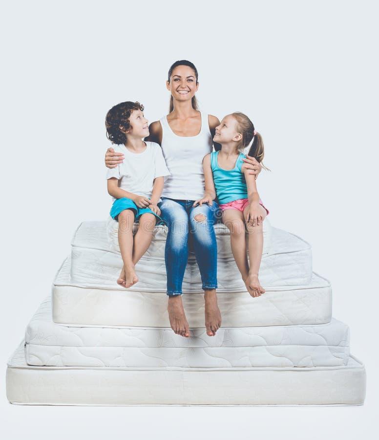 Crianças com a mãe que senta-se na pirâmide do colchão fotografia de stock
