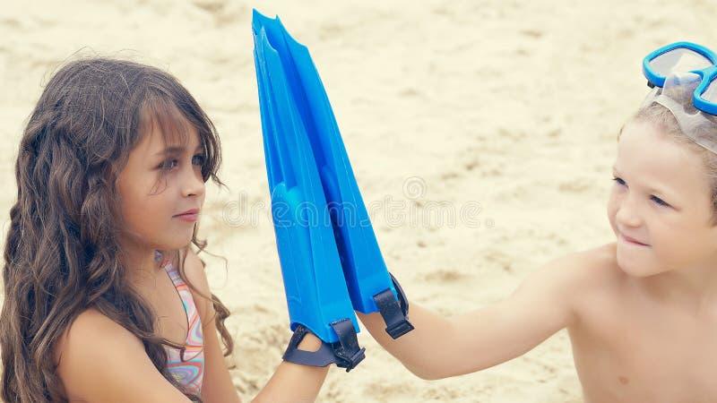 Crianças com mergulhar o equipamento que senta-se na areia na praia tropical e que joga com as aletas nas mãos foto de stock royalty free
