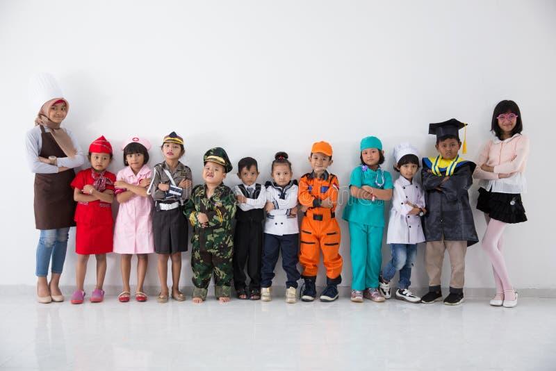 Crianças com o multi uniforme diverso da profissão foto de stock royalty free