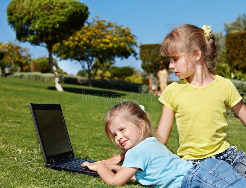 Crianças com o portátil na grama verde. fotos de stock royalty free