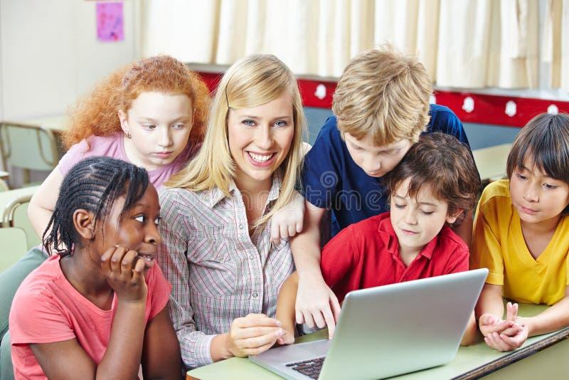Crianças com o professor no computador fotos de stock