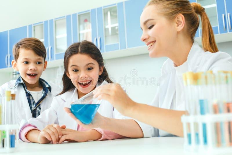 Crianças com o professor no resultado do laboratório da escola foto de stock