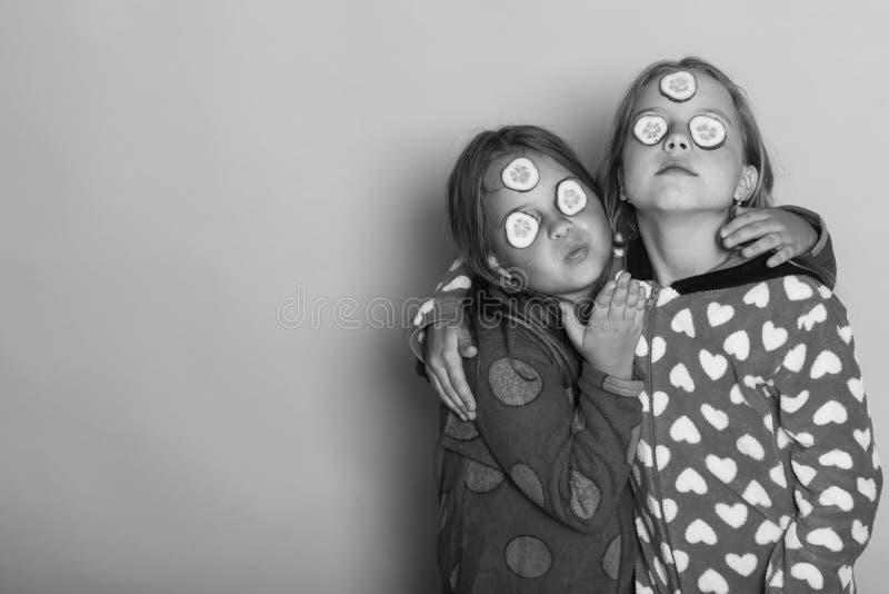Crianças com os pepinos nas caras e no cabelo fraco As crianças levantam no fundo cor-de-rosa que envia beijos, copiam o espaço foto de stock royalty free