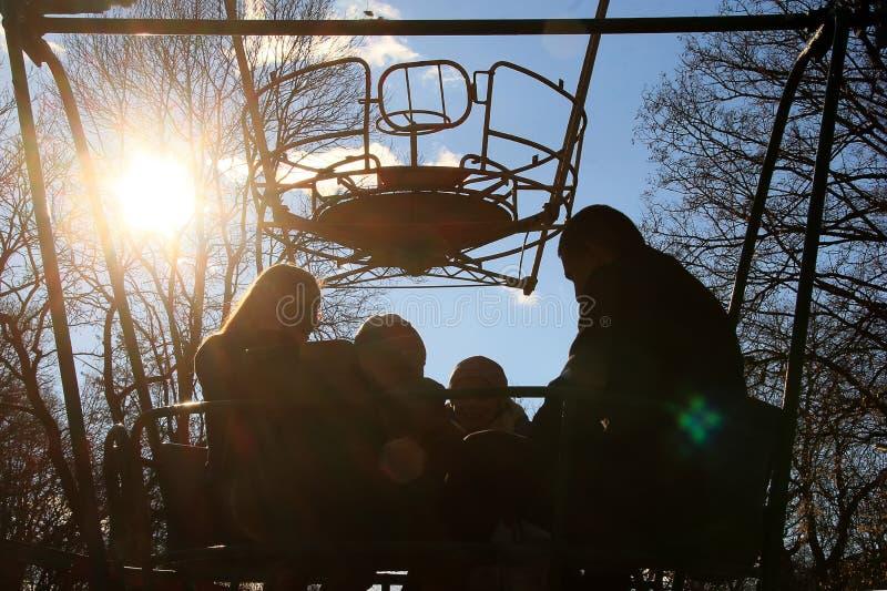 Crianças com pais em um carro de vista em um parque de diversões na mola adiantada imagem de stock