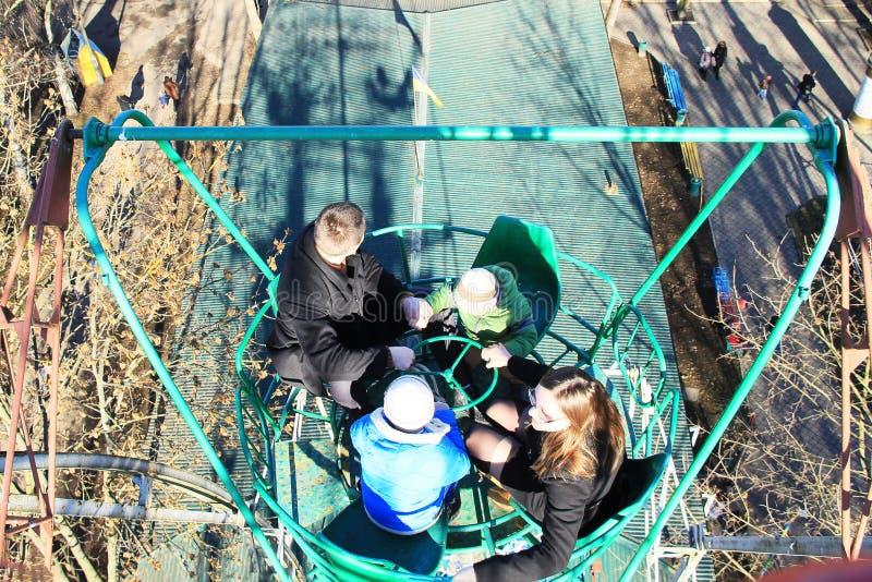 Crianças com pais em um carro de vista em um parque de diversões na mola adiantada imagem de stock royalty free