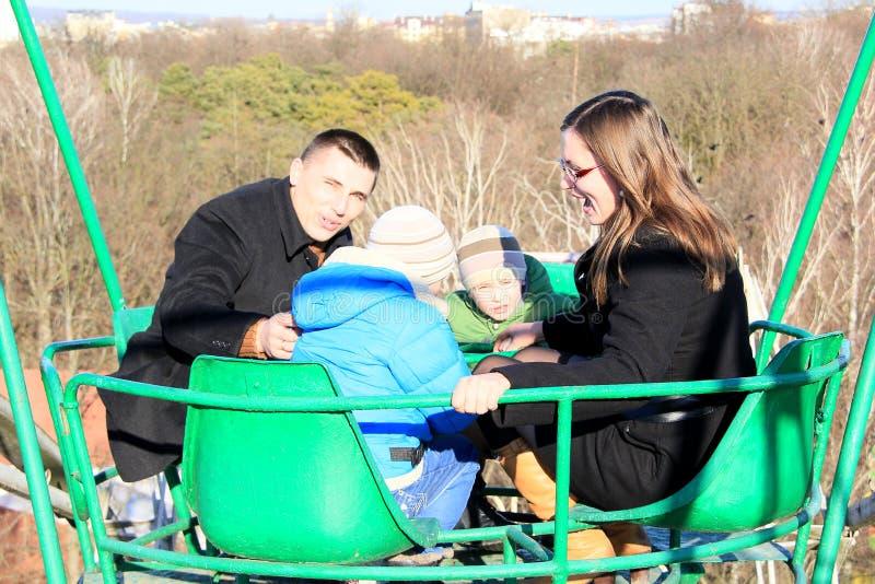 Crianças com pais em um carro de vista em um parque de diversões na mola adiantada fotografia de stock