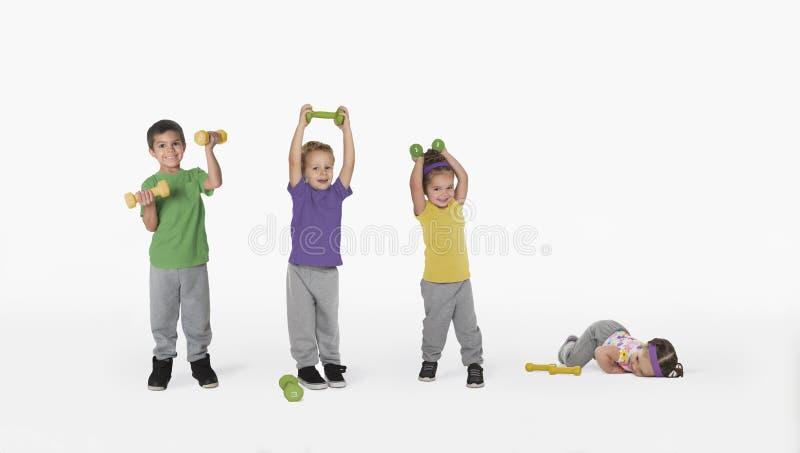 Crianças com pesos e um bebê cansado foto de stock