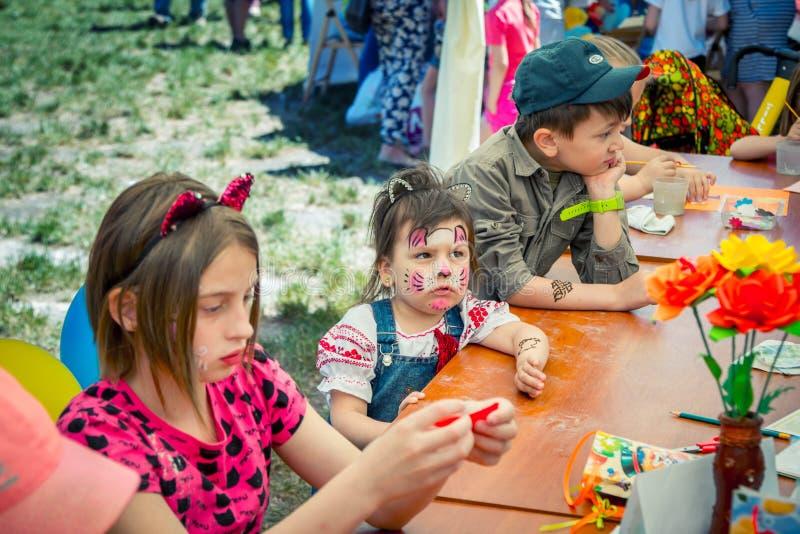 Crianças com pinturas engraçadas da cara que participam na oficina exterior da arte e do ofício imagens de stock royalty free