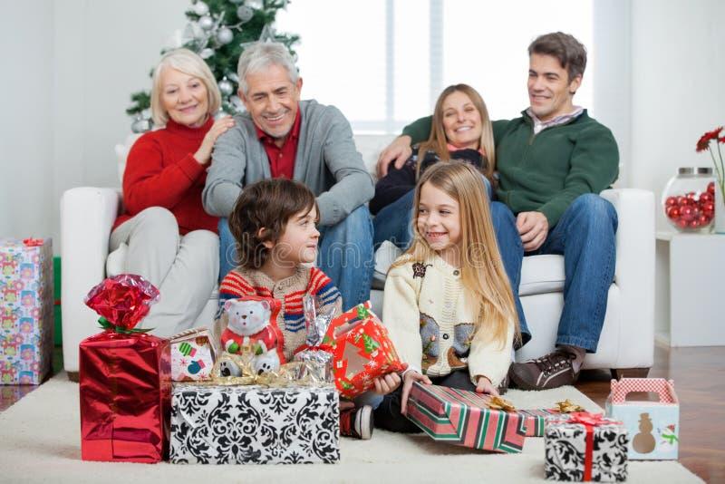 Crianças com presentes de Natal quando família foto de stock royalty free