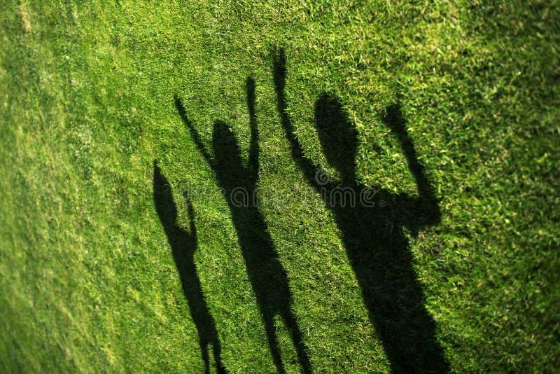 Crianças com suas sombras na grama silhuetas de três pessoas que estão com suas mãos esticadas acima foto de stock