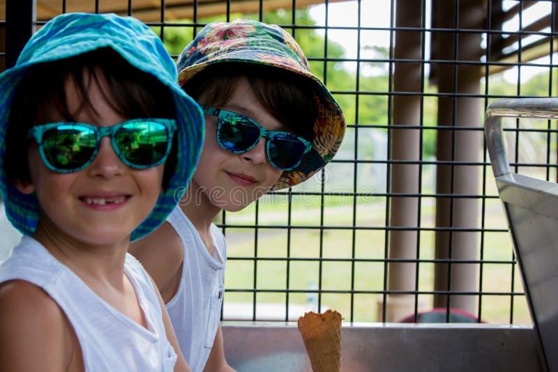 Crianças, comendo o gelado, ao sentar-se em um caminhão do safari imagens de stock royalty free